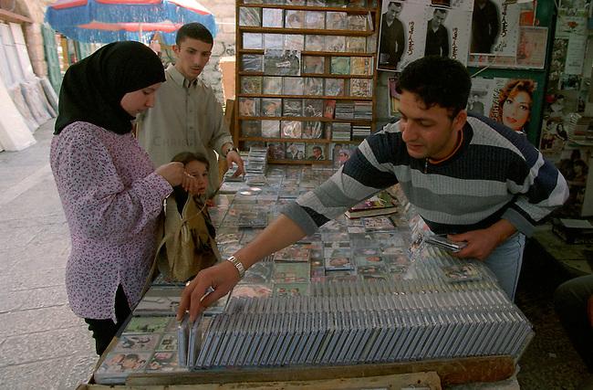 Strassenszene in Betlehem<br /> Immer wieder wird die palaestinensische Stadt Betlehem von der israelischen Armee belagert. Zum Teil tagelang duerfen die Bewohner ihre Haeuser nicht verlassen. Etliche Bewohner verloren bei den Kaempfen im April/Mai 2002 Angehoerige. Es gebe keine Familie in der heiligen Stadt, die nicht einen Toten zu beklagen habe, erzaehlen die Menschen. In den Tagen ohne israelische Soldaten, erweckt die Stadt einen normalen Anschein. Die Menschen gehen ihrem taeglichen Leben nach. Allerdings sind Touristen in diesen Tagen in der heiligen Stadt nicht zu sehen. Die Strassen sind so gut wie leer, die Wirtschaft liegt brach.<br /> Hier: CD- und Musikkassttenhaendler in der Altstadt. Alle erdenklichen Raubkopien an Musik und Computerprogramme sind hier erhaeltlich.<br /> 19.05.2002, Betlehem<br /> Copyright: Christian-Ditsch.de<br /> [Inhaltsveraendernde Manipulation des Fotos nur nach ausdruecklicher Genehmigung des Fotografen. Vereinbarungen ueber Abtretung von Persoenlichkeitsrechten/Model Release der abgebildeten Person/Personen liegen nicht vor. NO MODEL RELEASE! Nur fuer Redaktionelle Zwecke. Don't publish without copyright Christian-Ditsch.de, Veroeffentlichung nur mit Fotografennennung, sowie gegen Honorar, MwSt. und Beleg. Konto: I N G - D i B a, IBAN DE58500105175400192269, BIC INGDDEFFXXX, Kontakt: post@christian-ditsch.de<br /> Bei der Bearbeitung der Dateiinformationen darf die Urheberkennzeichnung in den EXIF- und  IPTC-Daten nicht entfernt werden, diese sind in digitalen Medien nach &sect;95c UrhG rechtlich geschuetzt. Der Urhebervermerk wird gemaess &sect;13 UrhG verlangt.]