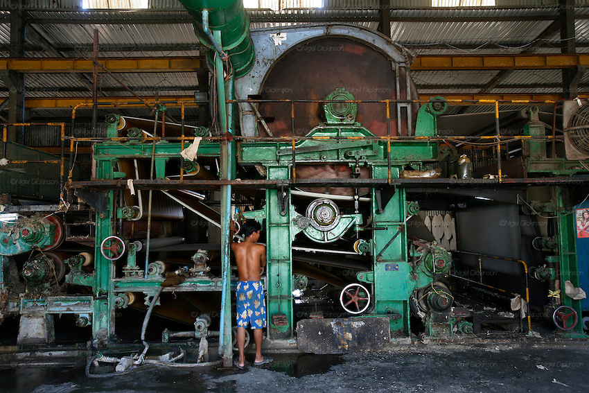A huge machine, resembling a steam engine, conveys the wet slurry of paper through driers and presses until out comes a perfect brown grey roll of paper. Recycling factory for cardboard and waste paper on the outskirts of Phnom Penh. This is the biggest recycling factory for cardboard in Cambodia. The paper is mixed with water, into mulch, then the sticky mixture is laid up a belt which goes through various drying and cleaning procedures. The end product, a grey coloured paper is used primarily in corrugated cardboard filling. However most of the carboard is exported to Thailand and Vietnam
