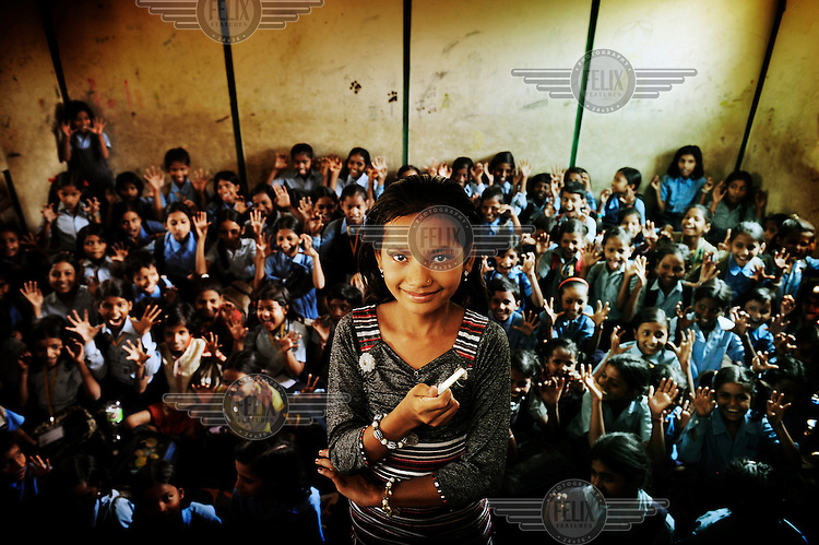 """Dewi stands in front of her class holding a piece of chalk. .Dewi is 12 years old and lives with her parents and sister in one of the slums in Delhi. She's very chatty and very disciplined. She has a lot of friends with whom she likes to play hide and seek. """"When I grow up, I want to be a teacher. Then I can teach children to read, write and count. This is very important for them since otherwise they won't get a job. I'll be a strict teacher and the kids will have to listen to me!"""".."""