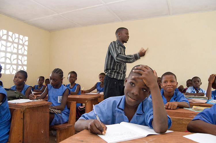 Nyanda F. Baimba at Kola Tree Community School. Behind him is the teacher, Mr. Gibril Koroma. Western Area, Sierra Leone