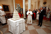 President George W. Bush and Mrs. Laura Bush lead the celebration of the 81st birthday of Pope Benedict XVI as he's presented a cake by White House Pastry Chef Bill Yosses Wednesday, April 16, 2008, at the White House.  White House photo by Eric Draper.