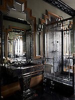 The opulent bathroom is clad in Art Deco style dark marble panelling, its geometric edges wrapped in metal and fluted boarders