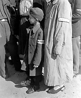 Six-year-old war orphan with Buchenwald badge on his sleeve waits for his name to be called at roll call at Buchenwald camp, Germany for departure to Switzerland.  June 19, 1945.  Pfc. G. A. Haynia. (Army)<br /> NARA FILE #:  111-SC-208199<br /> WAR & CONFLICT BOOK #:  1109