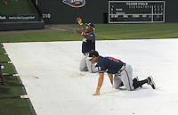 Infielder William Beckwith (48) and outfielder Will Skinner (26) of the Rome Braves crawl across the tarp to get a ball during a lengthy rain delay before a game against the Greenville Drive on July 5, 2012, at Fluor Field at the West End in Greenville, South Carolina. The game eventually was postponed due to rain. (Tom Priddy/Four Seam Images)