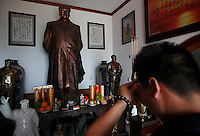 "Tian Haiming, a ""Red"" memorabilia collector and manufacturer, offers incense to statues of the Chairman placed in Tian's home near Mao's birthplace in Shaoshan, Hunan Province, China on 12 August 2009."
