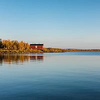 Red cabin of Sitojaure hut on lake Sitojaure, Kungsleden trail, Lapland, Sweden