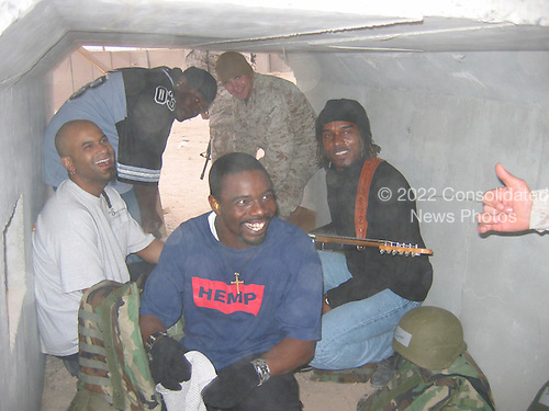 """""""Off the Wall,"""" a Los Angeles band, got a taste of daily life in Iraq when an explosion from a controlled detonation briefly halted the performance on December 24, 2004 and sent the band members scrambling for a protective bunker. The Marines in attendance barely budged. Letterman, along with his musical director Paul Shaffer and stage manager Biff Henderson, brought the popular late night television show to the Marines, sailors and soldiers currently stationed at Camp Taqaddum, Iraq. They were followed with a performance from """"Off the Wall,"""" a southern California band, which added to the holiday festivities. .Mandatory Credit: Linda Vong / USMC via CNP"""