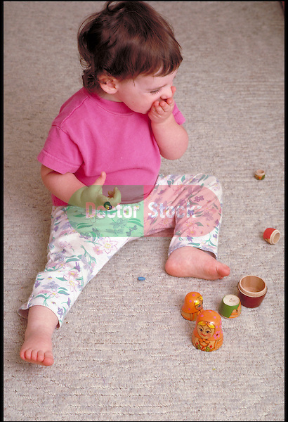 toddler girl playing with nesting dolls