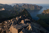 Hiker on rocky summit of Hermannsdalstind with mountains of Moskenesøy in the distance, Lofoten Islands, Norway