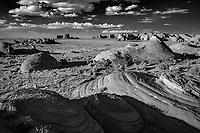 A black and white infrared image from Monument Valley.<br /> <br /> Monument Valley on the Utah and Arizona border is one of the most majestic places on earth. This great valley boasts sandstone masterpieces that tower at heights of 400 to 1,000 feet. framed by scenic clouds casting shadows that graciously roam the desert floor. Monument Valley is a Navajo Tribal Park and a frequent a filming location for Western movies.