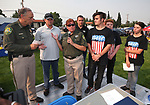Carson City Sheriff Ken Furlong and DARE Officer Lisa Davis thank Chris Sieben, with RCM Realty Group, during at the 16th annual National Night Out event, hosted by the Carson City Sheriff's Office, in Carson City, Nev., on Tuesday, Aug. 7, 2018. RCM Realty Group presented Davis with a check for $9800 raised during at a recent golf tournament at Toiyabe Golf Club in support of local youth programs like DARE, Stellar Squad, Cops &amp; Kids and National Night Out.<br />