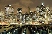 AVAILABLE FROM JEFF AS A FINE ART PRINT.<br /> <br /> AVAILABLE FROM CORBIS FOR COMMERCIAL AND EDITORIAL LICENSING.  Please go to www.corbis.com and search for image # 42-27340229.<br /> <br /> Lower Manhattan Business District Skyline and Wooden Posts in the East River, Illuminated at Night, New York City, New York State, USA