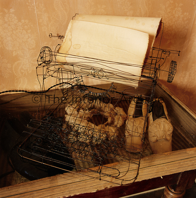 A wire-work model of a typewriter stands on a glass cabinet. A pair of antique shoes are displayed inside.