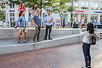 Woman taking picture of her five friends in Harvard Square