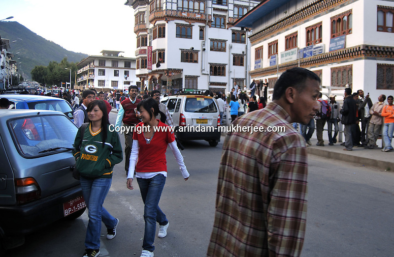 Two Bhutanese young lady wearing western cloth at Thimpu Market. Bhutan which was a consevative country about their customs and cultures now slowly adapting westernised culture as a result of globalisation. Arindam Mukherjee..