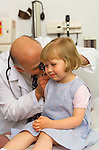 older, elder male doctor examining ear of 3 year old girl with otoscope