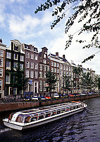 A tour boat cruises a canal in Amsterdam; traditional Dutch architecture is represented by the buildings lining the waterway. Amsterdam, The Netherlands.