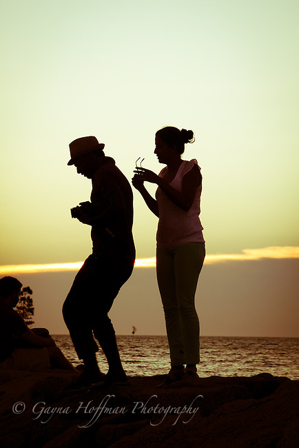 Man & woman in silhouette, taking picture of sunset.