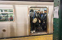 An NYPD officer is seen on a subway train in New York on Saturday, March 5, 2016. The NYPD announced an effort to combat a spike in crimes, particularly slashings, in the subway by having more officers on trains and platforms. An officer will be on every train from 8 PM to 4 AM, a plan that was used years ago. Crime in the subway is up 25% compared to last year. (© Richard B. Levine)
