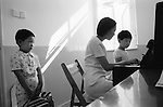 The Peoples Republic of China. Shanghai. At the Shanghai Arts Kindergarten a student waits his turn for a piano lesson. It seems that in China, as in the rest of the world, piano lessons are more popular with parents than with children. FROM THE BOOK SHANGHAI ODYSSEY BY HOMER SYKES WITH THE SUPPORT OF THE GRIMSTONE FOUNDATION. PUBLISHED BY DEWI LEWIS PUBLISHING ISBN 1-89923514-0