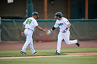 Lynchburg Hillcats manager Rouglas Odor (24) congratulates second baseman Dillon Persinger (38) after hitting a home run during the first game of a doubleheader against the Potomac Nationals on June 9, 2018 at Calvin Falwell Field in Lynchburg, Virginia.  Lynchburg defeated Potomac 5-3.  (Mike Janes/Four Seam Images)