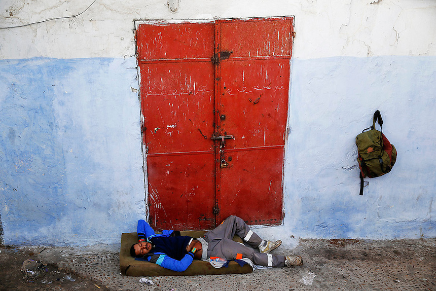 "A man sleeps in front of a closed shop in Rabat's Medina September 23, 2014. Behind walls of Medina and Kasbah of the Oudayas, ancient neighbourhoods of Morocco's capital, labyrinths of small alleys, colourful buildings and street markets offer a glimpse into city's rich history. Rabat was recently listed by UNESCO as a World Heritage Site and suggested as a ""must see"" destination by major media outlets and tourist agencies.  REUTERS/Damir Sagolj (MOROCCO)"