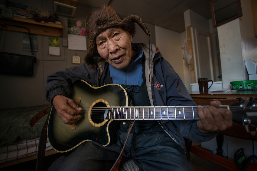 79-year-old Alexie Gusty plays guitar in his home in Stony River, Alaska. Photo by James R. Evans