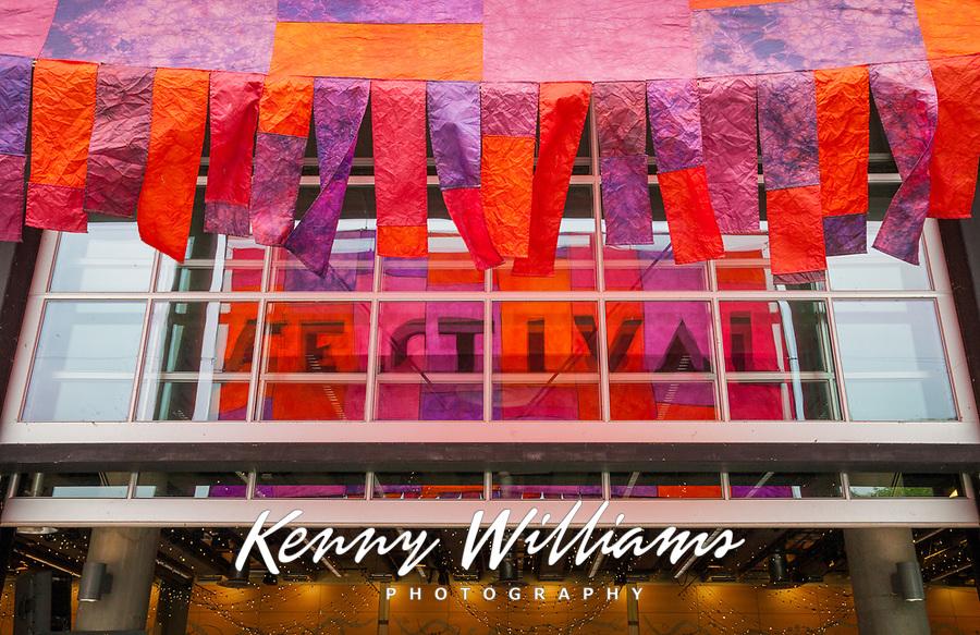 Colorful banners reflecting on glass window panels, Northwest Folklife Festival 2016, Seattle Center, Washington, USA.