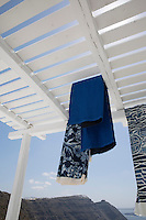 Lengths of fabric hang from the slatted wooden pergola that shades the terrace