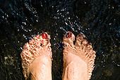 Feet in clear stream water.