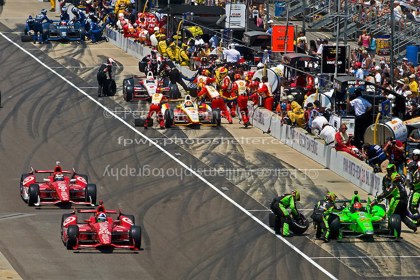 Dario Franchitti (#50) and teammate Scott Dixon (#9) exit the pits following a stop.