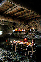 The faces of the two little girls are illuminated by the candles that decorate the rustic wooden table in this hay-strewn barn