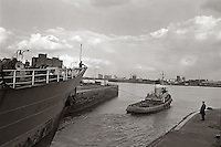 A ship leaves the West India Dock, heading down river to the sea.