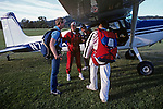 Instructor getting a student ready to tandem jump out of a small aircraft checking equipment before getting in plane.