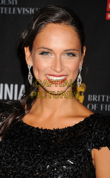 Asha Leo.BAFTA Los Angeles 2011 Britannia Awards held at the Beverly Hilton Hotel, Beverly Hills, California, USA..November 30th, 2011.headshot portrait red lipstick smiling dangling silver earrings black sequins sequined  .CAP/ROT/TM.©Tony Michaels/Roth Stock/Capital Pictures