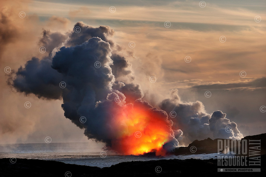 At sunset, explosions and steam clouds mark where lava from Kilauea Volcano reaches the Pacific Ocean at Kalapana, Big Island.