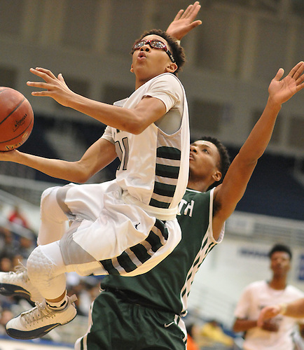 Jevon Santos #11 of Elmont, left, makes an acrobatic move attempting to drive to the net during the Nassau County varsity boys basketball Class A semifinals against Valley Stream North at Hofstra University in Hempstead, NY on Wednesday, March 1, 2017. Elmont won by a score of 67-50.