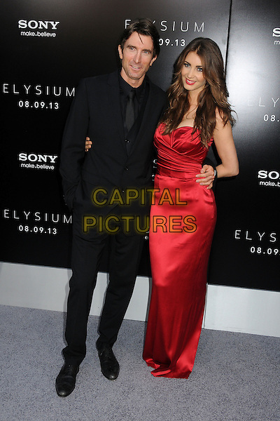 Sharlto Copley &amp; Tanit Phoenix<br /> &quot;Elysium&quot; Los Angeles Premiere held at the Regency Village Theatre, Westwood, California, USA.<br /> August 7th, 2013<br /> full length black suit red silk satin dress couple <br /> CAP/ADM/BP<br /> &copy;Byron Purvis/AdMedia/Capital Pictures
