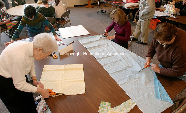 HARWINTON, CT - 26 FEBRUARY 2004 - 022605JS08--Volunteers at the chief cutting station, clockwise from left, Beverly Neski of Harwinton, Mary Winar of New Hartford, Lori Schneider of New Hartford and Connie Novak of Torrington, cut material to size to be used as kerchiefs for cancer patients during a workshop Saturday at the Immaculate Heart of Mary Church in Harwinton. The group is part of the Cheshire-based CUREChief program.  --Jim Shannon Photo --Immaculate Heart of Mary Church; Harwinton; CUREChief; Beverly Neski, Mary Winar, Lori Schneider, Connie Novak, Torrington are CQ