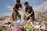 Children earning income collecting plastic and recyclables in trash, Kabul, Afghanistan