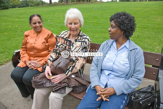 Group of older woman sitting on bench in the park chatting,