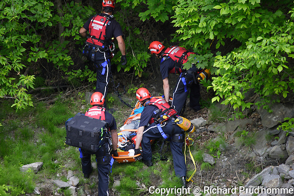 Rescue workers removing injured man from side of river in Joliette, Quebec
