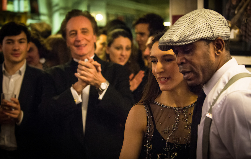 Jelly Germain (tap dancer) and Caroline Podetti dancing, with Jean-Paul Amouroux (Boogie-Woogie pianist) in the background, during a Paris Boogie Speakeasy soirée hosted by Yves Riquet for members of Cambridge University and others at 256 Rue Marcadet, Paris. Paris Boogie Speakeasy is a private jazz and cocktail club founded, run and owned by Yves Riquet. Judged by l'Express as being one of the top ten most exciting private locations in Paris, Paris Boogie Speakeasy has created the artistic and intellectual euphoria of the inter war années folles, with New Orleans, Boogie Woogie, Charleston and Blues music from that era, speakeasy cocktails and a scintillating range of musicians, dancers and guests. Friday 12th December 2014.