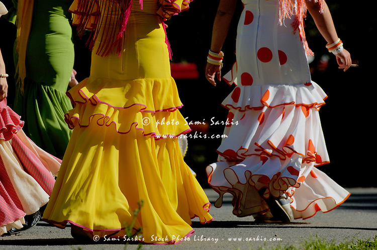 Women in flamenco dress walking through Maria Luisa Park towards the Seville Spring Fair, Seville, Andalusia, Spain.
