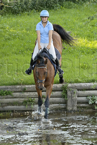 01 09 2005, Germany. Horsewoman  at the Water Obstacle at an Equestrian sports event. Model Released