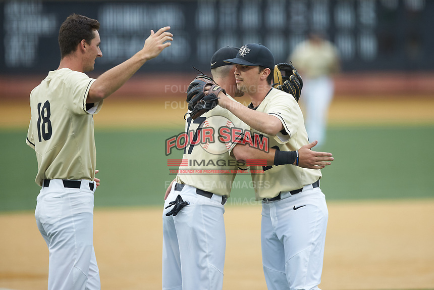 Wake Forest Demon Deacons senior pitcher Ben Casstevens (20) gets a hug from Bruce Steel (17) as he walks off the field during the game against the Miami Hurricanes at David F. Couch Ballpark on May 11, 2019 in  Winston-Salem, North Carolina. The Hurricanes defeated the Demon Deacons 8-4. (Brian Westerholt/Four Seam Images)
