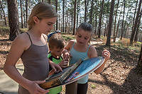NWA Democrat-Gazette/ANTHONY REYES @NWATONYR<br /> Sherine Raines of Pea Ridge with her children Rylee (from left), 10, Raelynn, 9, and Ramsey, 6, read a marker Tuesday March 21, 2017 about the topography of the Ozarks while walking the Ozark Plateau Trail at Hobbs State Park in Rogers. The trio was at the park with their family to enjoy the nice weather and learn a little about the park and nature. The park has several spring break activities planned through the week including scavenger hunts and nature hikes. Contact the visitors center (479) 789-5000 for more information.