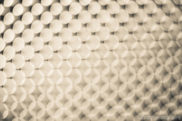 Creative black and white abstract of holes in a cheese grater