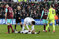 Ki Sung-Yueng of Swansea City (C) reacts with Andre Ayew of Swansea City who lays on the ground after being fouled and winning a penalty during the Premier League match between Swansea City and West Ham United at The Liberty Stadium, Swansea, Wales, UK. Saturday 03 March 2018