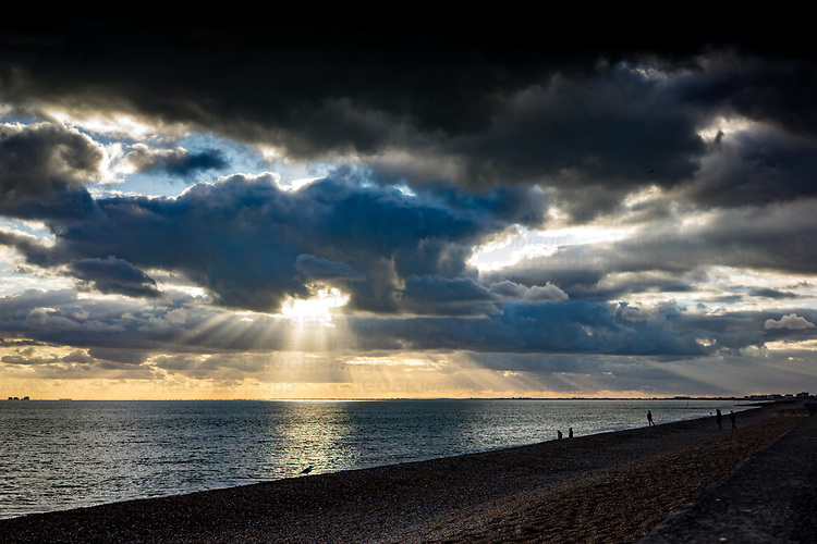 Stormy skies over the seafront in Hythe, Kent, England with figures on the beach under a dramatic sunset